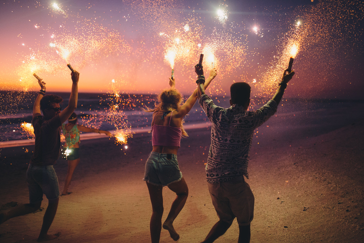 People waving sparklers on beach
