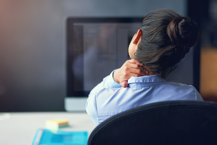 Rear view shot of a person in dress shirt with a ponytail rubbing neck while seated at a desk in front of a computer