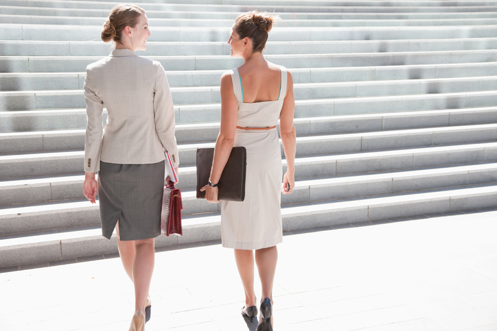 Rear view of two people in business skirt suits heading toward stairs while talking, standing tall