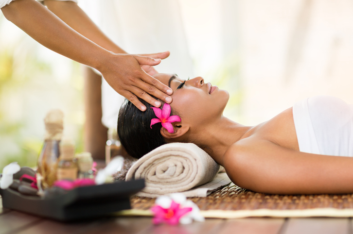 Relaxed person with flower behind ear lies on massage mat with eyes closed as head is massaged