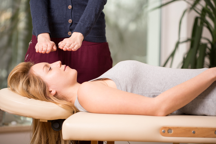 Energy healer holds hands above body of client lying on massage table