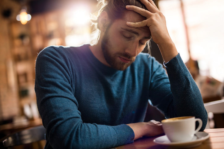 Stressed and holding head in pain in a cafe with cup of coffee ignored on table