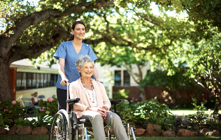Nurse in scrubs pushes mature adult in pink top and necklaces in wheelchair under shaded area with trees