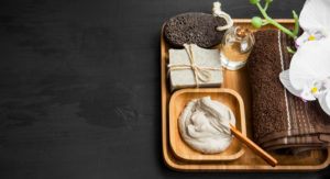 Wooden tray of spa clay, soap, towel, and oil arranged neatly