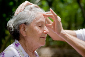 Senior woman sits outside while person's hand is massaging her forehead in front of background of trees