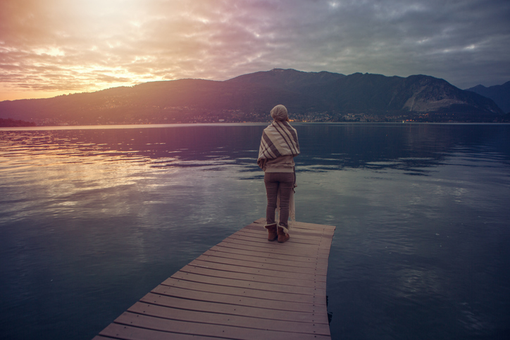 Standing on lake pier looking at view at dawn wrapped in blanket