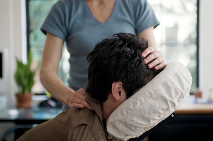 Person receives chair massage for neck injury