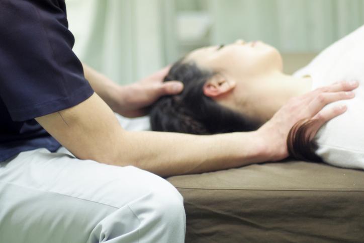 Woman receiving Jin Shin Do acupressure massage on shoulder