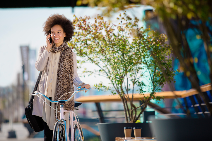 Smiling person in spring outfit and scarf talks on phone with smile while walking bright blue bike along path in city
