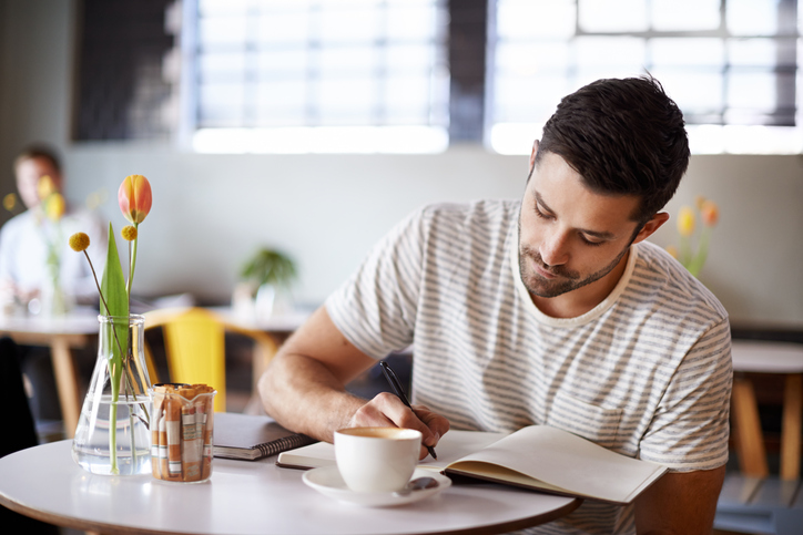 Person with short hair and facial hair sits at table with coffee and writes in journal