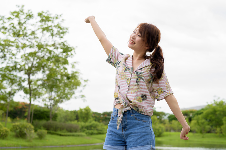 Young person in shorts with ponytail raises arms and does stretch outside near trees
