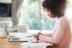 Cropped shot of a young person in pink sweater working on her laptop at home