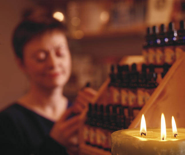 candle in foreground with person and essential oils