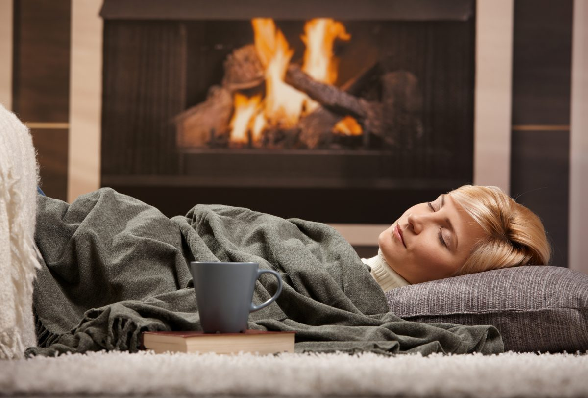 Woman asleep in front of the fireplace
