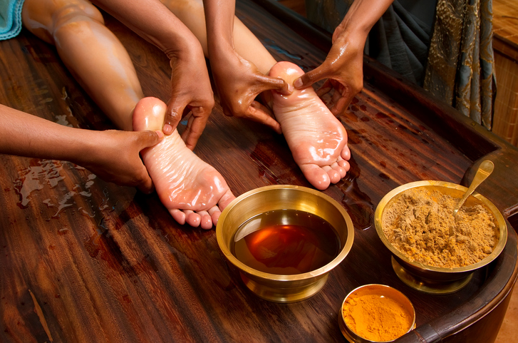 Two massage therapists perform Ayurvedic massage with oils on client's feet