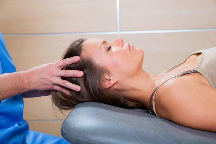 Hands of massage therapist on top of head of person with short brown hair in tan tank top