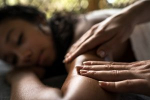 Close up of human hands massaging a person outdoors at the spa.