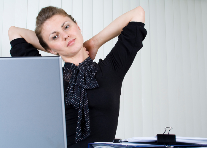 Woman stretching and rubbing back of neck while seated at computer