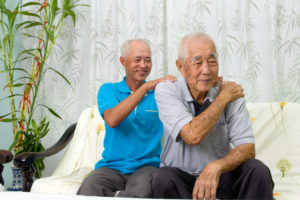 Elderly man holds shoulder while mature adult provides massage in room of house