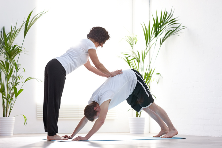 Instructor helping client in yoga pose