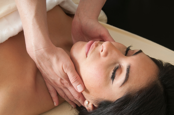 Close-up image of woman lying on massage table receiving lymphatic massage on nect