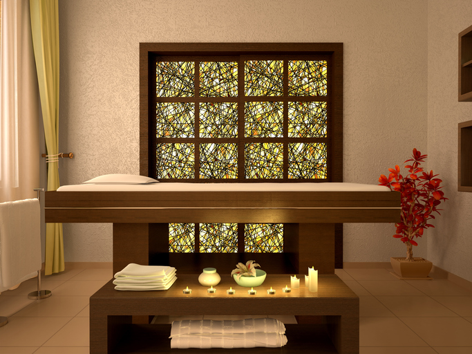 Photo of calming, well-organized massage room in neutral browns with soft light