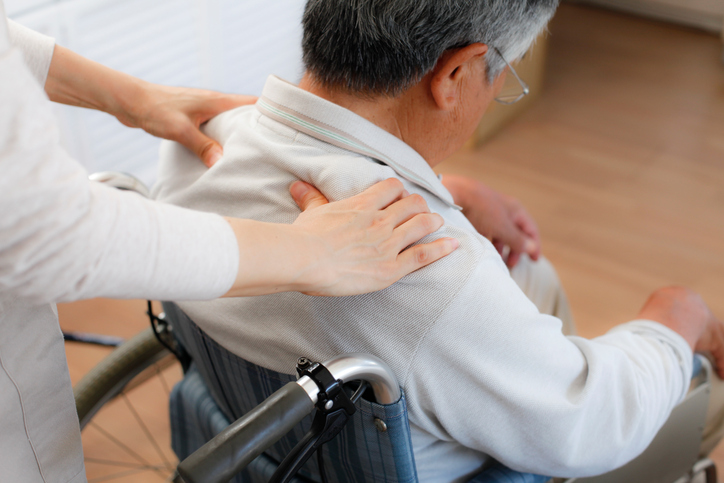 Person seated in wheelchair receives shoulder massage from professional