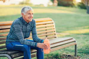 Senior sportswoman sitting on a bench in the park