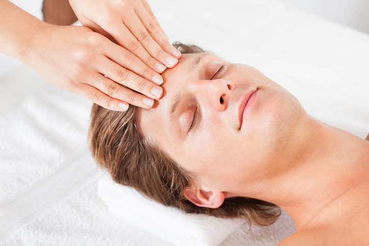 Adult with short hair receives massage on forehead with eyes closed