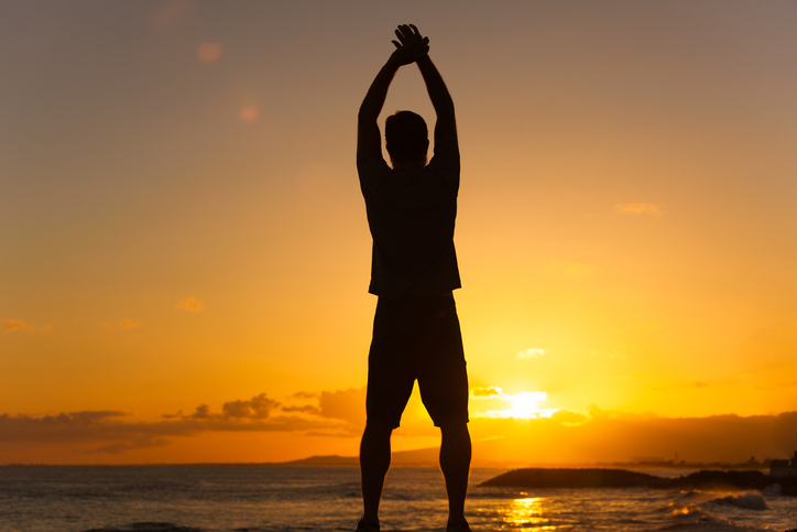 Rear view photo of person with short hair and muscular build stretching both arms up looking out to sea